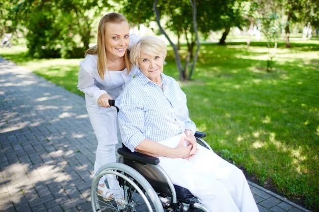 uśmiechnięta starsza pani na wózku inwalidzkim z opiekunką